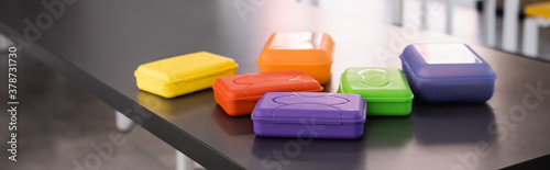 Valokuvatapetti horizontal image of colorful plastic lunch boxes on table in school dining room