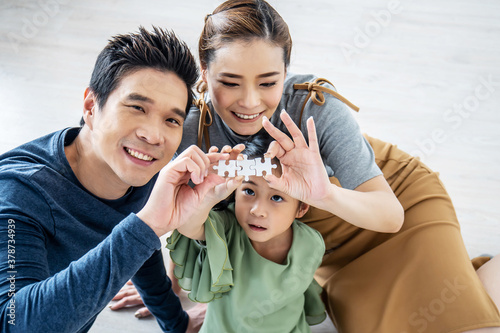 Fototapeta Happy family, Asian little daughter playing jigsaw puzzle with her mother and father for family concept, They assembling Jigsaw Puzzle.. obraz