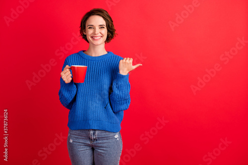 Fototapeta Portrait of her she nice attractive pretty glad cheerful cheery brown-haired girl drinking cacao demonstrating copy space solution advert isolated over bright vivid shine vibrant red color background obraz