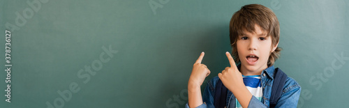 Website header of excited schoolboy pointing with fingers at green chalkboard