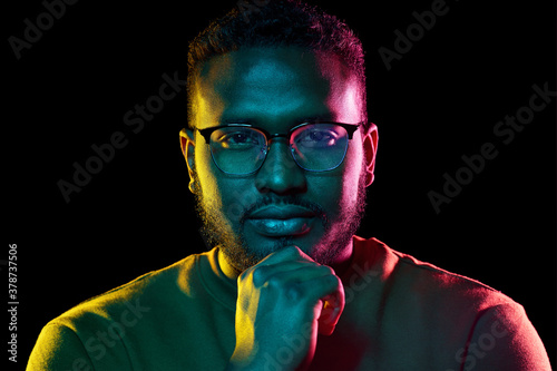Fototapeta people and ethnicity concept - portrait of young african american man in glasses over black background obraz