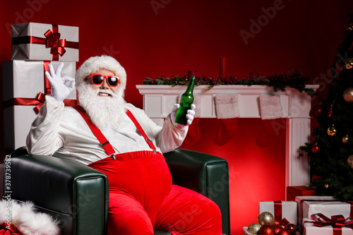 Fototapeta Stylish fat santa claus sit chair show ok sign hold beer have x-mas fireplace tradition present box ornament isolated over bright shine color background obraz