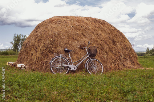 Obraz na plátně Bicycle in a field near a haystack