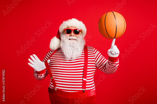 Fototapeta Portrait of his he nice handsome attractive cheerful cheery fat overweight Santa grandfather spinning ball on forefinger having fun isolated over bright vivid shine vibrant red color background obraz