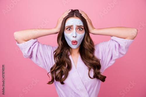 Photo portrait of amazed surprised upset girl with cosmetic mask on face keeping hands on head shocked isolated on pink color background
