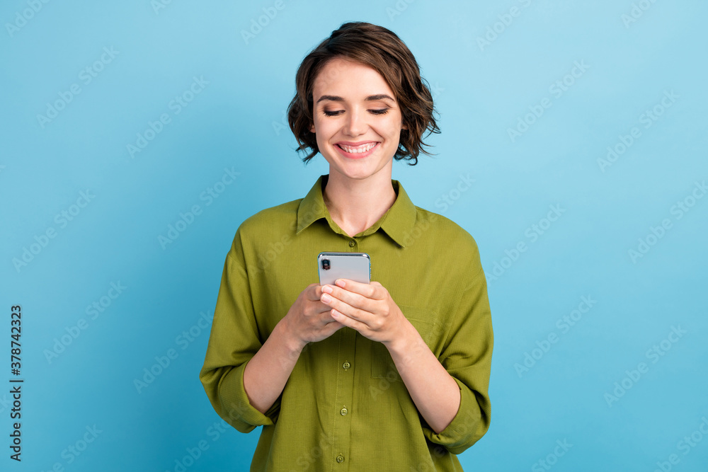 Fototapeta Photo of charming cute lady short hairstyle arms hold telephone look screen cheerful beaming smile read chatting text wear green shirt isolated blue color background