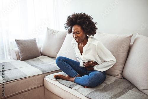 Sad beautiful woman sitting on the couch and feeling spasm and symptoms of pms Tapéta, Fotótapéta