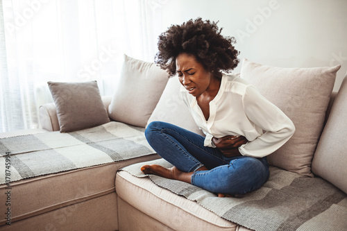 Obraz View of young woman suffering from stomachache on sofa at home. Woman sitting on bed and having stomach ache. Young woman suffering from abdominal pain while sitting on sofa at home - fototapety do salonu