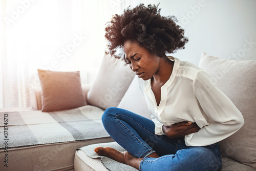 Fototapeta View of young woman suffering from stomachache on sofa at home. Woman sitting on bed and having stomach ache. Young woman suffering from abdominal pain while sitting on sofa at home obraz
