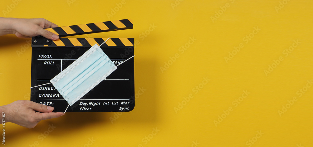 Black with yellow Clapper board or movie slate with face mask. it use in video production and cinema industry on yellow background.