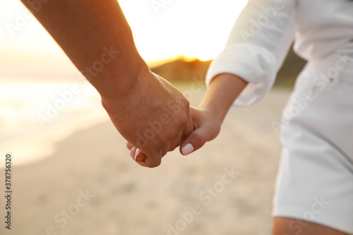 Lovely couple holding hands on beach, closeup
