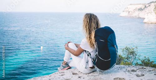 Back view of female explorer with travel backpack enjoying natural environment o Fototapet