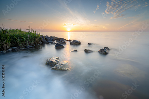 Fototapeta Inspirational and endless sunrise on the coast of a large inland lake in the net