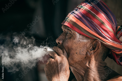 Countryside, old man sitting smoking. Dark background, close up portrait, Thailand.
