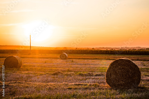 A field with haystacks on a summer or early autumn evening with a orange sky in the background Wallpaper Mural