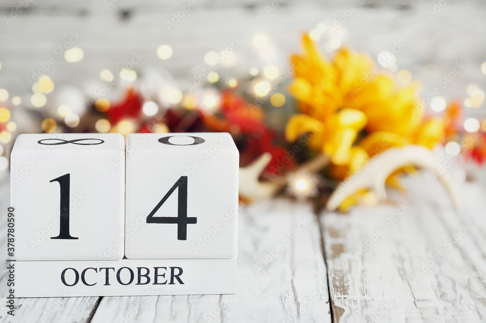 Fototapeta White wood calendar blocks with the date October 14th and autumn decorations over a wooden table. Selective focus with blurred background.