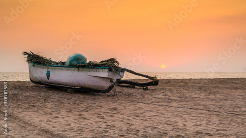 Fishing boat on the beach at dusk in Goa, India