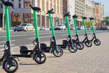 Eco Transportation Concept. Scooter Rental In The City. Environment Conservation. Eco Friendly Transportation. Vehicle Rent Service Concept. Electric Scooters In Line On Urban City Background