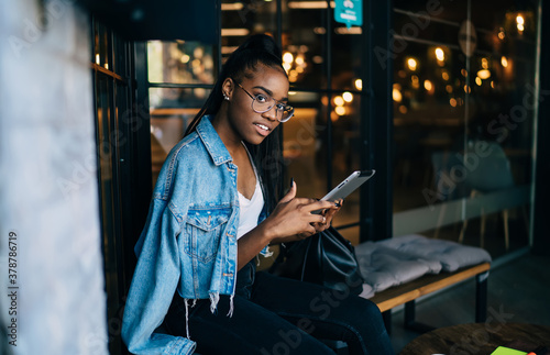 Fotografering Half length portrait of beautiful dark skinned woman in trendy wear using modern