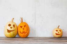 Halloween Pumpkins On Wooden Table On Background Old White Wall