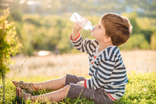 A beautiful child sitting on the grass drinks water from a bottle in the summer at sunset Wallpaper Mural