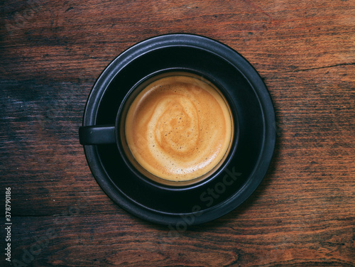 Fototapeta A cup of coffee on wooden desk background, top view obraz