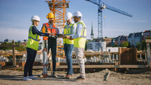 Diverse Team Of Specialists Use Tablet Computer On Construction Site. Real Estate Building Project With Civil Engineer, Architect, Business Investor And Surveyor With Theodolite Discussing Plans.