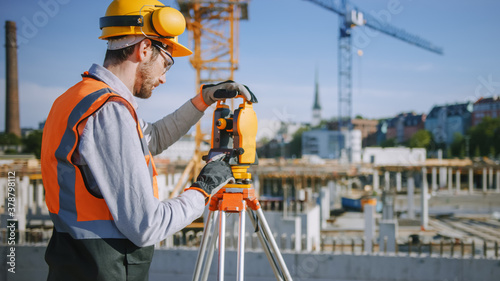 Construction Worker Using Theodolite Surveying Optical Instrument for Measuring Angles in Horizontal and Vertical Planes on Construction Site Wallpaper Mural