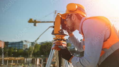 Fototapeta Construction Worker Using Theodolite Surveying Optical Instrument for Measuring Angles in Horizontal and Vertical Planes on Construction Site. Worker in Hard Hat Making Projections for the Building. obraz