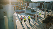 Diverse Team Of Specialists Taking A Walk Through Construction Site. Real Estate Building Project With Senior Civil Engineer, Architect, General Worker Discussing Planning And Development Details.
