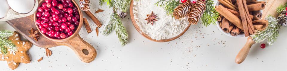 Fototapeta Boks Ingredients for Christmas cooking, winter baking cookies, gingerbread, fruitcake, seasonal drinks. Cranberries, dried oranges, cinnamon, spices, flour on white table, copy space top view