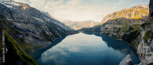 Fototapeta Idyllic panorama view of the lake Oeschinensee. Picture or postcard view of Oeschinen Lake by Kandersteg, Switzerland. Turquoise lake with steep mountains and rocks in background. Swiss Alps. obraz