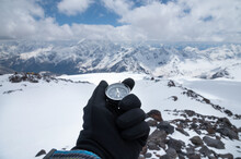 Magnetic Compass In A Man's Hand In A Glove Against The Background Of The Snow-capped Mountains Of The Caucasus In The Afternoon. Navigation Concept