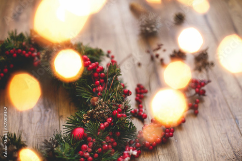 Christmas wreath decorations close up on rustic wood in lights.