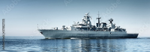 Fotografiet Large grey modern warship sailing in still water