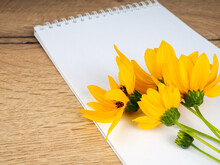 One Field Flower Is Lying On A Wooden Table Next To A Notebook An Empty Mockup. Blank Notebook With White Flower And Bas Ket Of Flower On Vintage Wooden Table View From Above With Copy Space