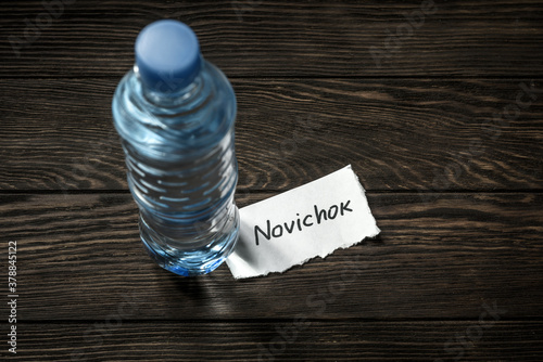 Bottle of water and note Novichok on wooden table Canvas Print
