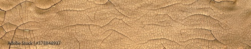 Fototapeta Detailed cracked soil showing a dry desert land scorched in the heat causing cracks