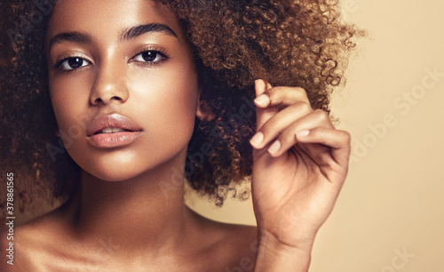 Beautiful black woman . Beauty portrait of african american woman with clean healthy skin on beige background.  Smiling beautiful afro girl.Curly black hair