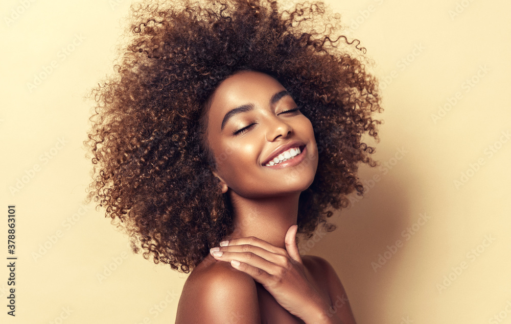 Fototapeta Beautiful black woman . Beauty portrait of african american woman with clean healthy skin on beige background.  Smiling beautiful afro girl.Curly black hair