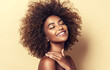 Leinwandbild Motiv Beautiful black woman . Beauty portrait of african american woman with clean healthy skin on beige background.  Smiling beautiful afro girl.Curly black hair