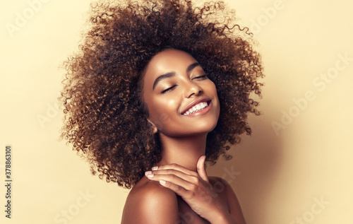Obraz Beautiful black woman . Beauty portrait of african american woman with clean healthy skin on beige background.  Smiling beautiful afro girl.Curly black hair - fototapety do salonu