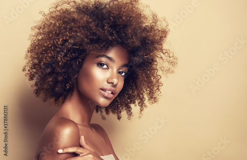 Fototapeta Beautiful black woman . Beauty portrait of african american woman with clean healthy skin on beige background.  Smiling beautiful afro girl.Curly black hair obraz