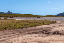 Car Tracks And A Rusting Wreck On Tidal Salt Flats