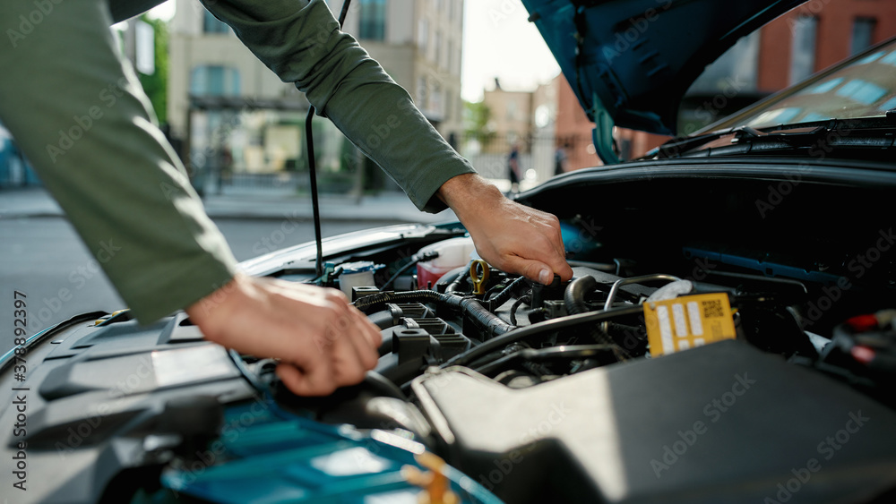 Fototapeta Close up of hands of young man examining broken down car engine, standing near his car with open hood on the city street