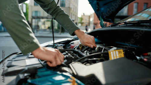 Fototapeta Close up of hands of young man examining broken down car engine, standing near h
