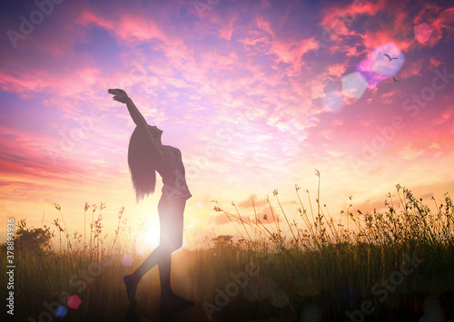 Individual human right day concept: Silhouette of healthy woman raised hands for praise and worship God at autumn sunset meadow background