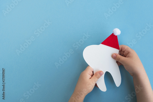 Photo Little child holding cute decorative tooth in a red Santa Claus hat on light blue background