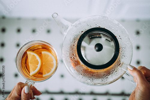 Modern glass teapot and cop of tea with lemon #378903730