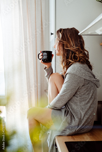 Young pretty woman drinks coffee sitting at her kitchen at home and looking out the window enjoys of morning. #378903773